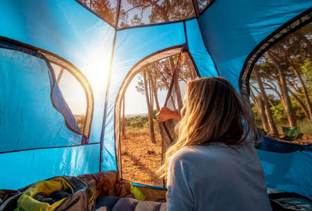 Morning in the Tent, Young Woman Woke up and Looks out at the Amazing Beauty of Nature. Enjoying Camping in the Mountainous Forest. Active Summer Holidays.