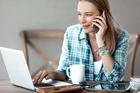 Portrait of a Beautiful Female Talking on the Phone and Drinking Morning Coffee near the Notebook. Young Successful Businesswoman Working from Home. Studying Online.