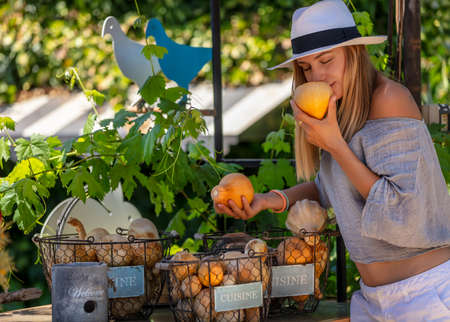 Happy Healthy Woman with Pleasure Spending Summer day at Outdoor Farmers Eco Market. Enjoying Aroma of a Fresh Ripe Little Pumpkin. Vegetarian Nutrition. Healthy Lifestyle. Banque d'images