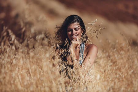 Portrait of a Cheerful Female. Model Laughing. Girl Stands in the Golden Wheat Field. Enjoys Summer Sunny Day. Outdoor Autumn Photoshoot.