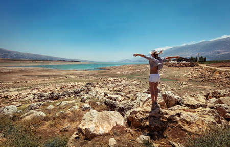 Happy Woman with Raised up Hands Standing Near Lakes and Enjoying Amazing View. Beautiful Stony Landscape in the midst of Valley. Travel Along Lebanon. Banque d'images