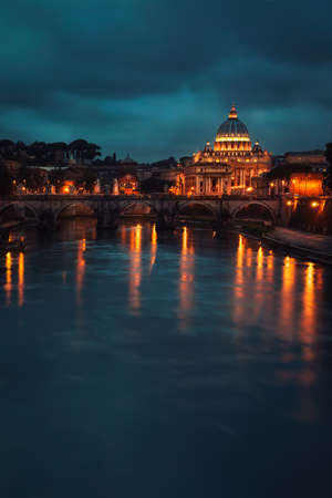 Beautiful night view on St. Peter's Basilica, glowing lights of the church reflected in the river, amazing European architecture of Italy, Rome, Vatican