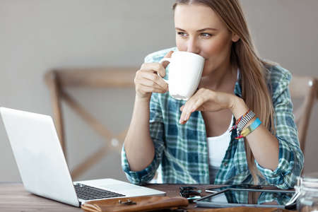 Beautiful Young Woman Working from Home. Pretty Female with Pleasure Drinking Coffee and Working on the Laptop. Freelancing. Banque d'images