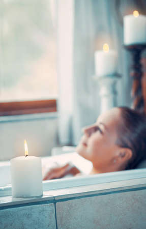 Selective focus on a candle, blurred woman on the background of an image, female with pleasure enjoys aroma candles, a day at spa, hygiene and relaxation concept