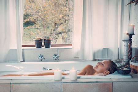 Happy woman at spa resort, nice female with closed eyes of pleasure taking bath, beauty and health treatment, spending vacation at wellness hotel Banque d'images