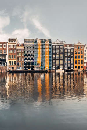 Dutch architectural landmark, also known as the dancing houses of Amsterdam, built on the canal of Damrak street, Amstel river, Netherlands or Holland Éditoriale