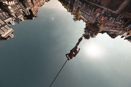 AMSTERDAM, NETHERLANDS: Unidentified man entertains curious crowd, performs tightrope walking, also called funambulism - the skill of walking along a thin wire or rope, June 17, 2019, Holland