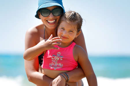 Portrait of a Beautiful Cheerful Mother Hugging her Cute Little Daughter on the Beach. Enjoying Time Together. Happy Summer Vacation.