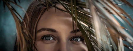 Portrait of a Beautiful Young Woman On Tropical Island In Vacation. Closeup Photo Of a Woman's Eyes Looking through Palm Leaves. Enjoying Exotic Nature. Banque d'images