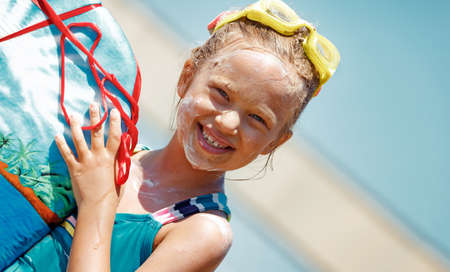 Portrait of a Nice Little Girl Wearing Water Goggles with Sunscreen on Face Holding Body Board. Spending Summer Vacation on the Sea. Happy Leisure Time on the Beach Resort. Healthy Sportive Childhood.