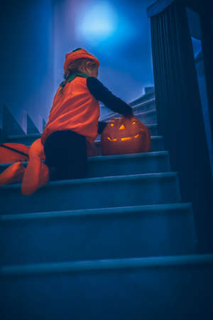 Little Baby Decorating Home Stairs with Beautiful Carved Gourds, Jack o Lanterns. Dressed as a Small Festive Pumpkin. Halloween Party. Traditional American Holiday.