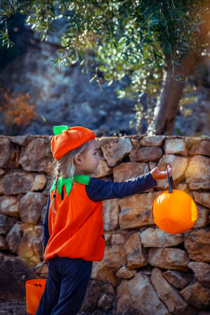 Halloween Celebration. Nice Little Baby Dressed in Pumpkin Character Outfit On The Way to Collect Candies from the Neighbors. Kids Enjoying Happy Autumn Holiday. Banque d'images