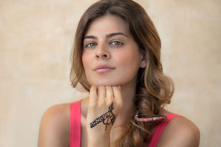 Portrait of an Attractive Woman Isolated on Beige Background with Beautiful Henna Drawing on the Hand. Stylish Body Art. Authentic Beauty of Young Female. Banque d'images