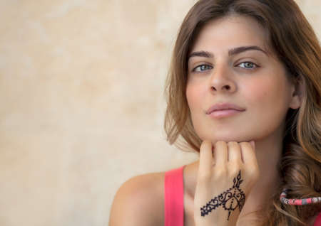 Portrait of an Attractive Woman Isolated on Beige Background with Beautiful Mehndi Drawing on the Hand. Stylish Body Art. Natural Beauty of Young Female. Photo with Copy Space. 版權商用圖片