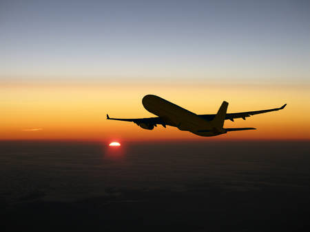 Large airliner silhouette climbing at sunset