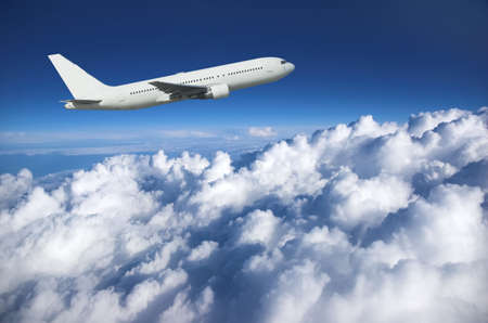 Large airliner climbing along cloud top against a deep blue sky Stock Photo