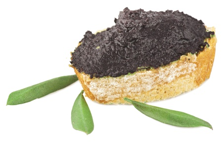 Patè of black olives with leaves on white photo