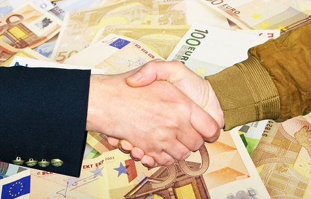 consent: Two businessmen shaking hands on the money background Stock Photo
