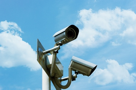 city surveillance: Security camera on the sky background