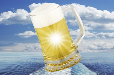 international beer: glass of blond beer on sea background