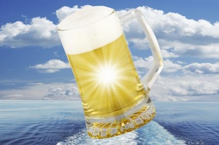 single beer bottle: glass of blond beer on sea background