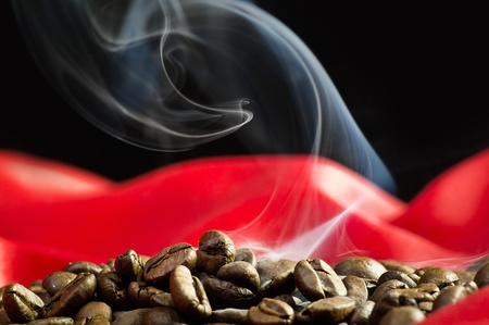 Steaming coffee beans close up on a red silk photo
