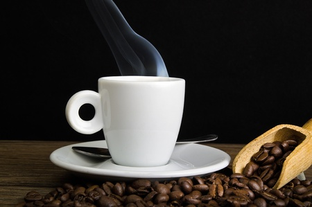 Steaming coffee and coffee beans close up Banque d'images