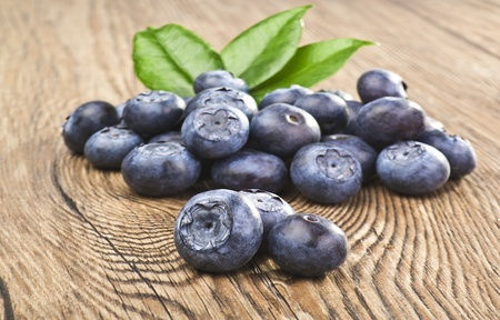 foglia: blueberries close up on a wood table