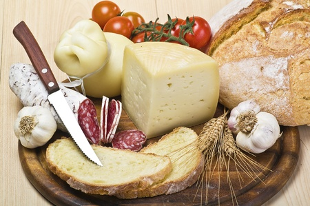 cutting board with cheese,salami and spices photo