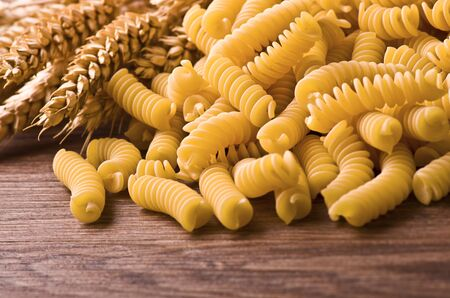 pileof  fusilli pasta on wood background  photo