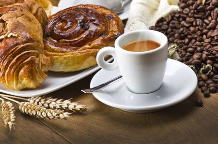 Coffee cup with a croissant and fresh coffee beans on a wood table