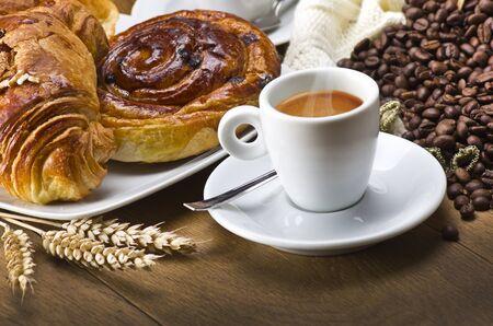 Taza de café con un croissant y granos de café recién hechos en una mesa de madera