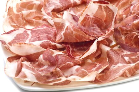 A plate of sliced italian coppa on white   photo