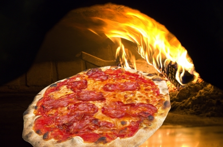 Pizza con salame caliente en un horno de pizza