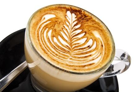 planta de cafe: taza de capuchino con un dise�o en el blanco Foto de archivo