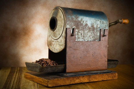 blackly: vintage roaster with coffee beans in the wood table Stock Photo