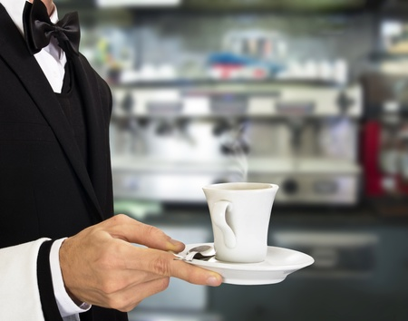 busboy: young waiter in work uniformon with coffee