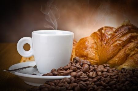 Caffè fumo sui chicchi di caffè e croissant sfondo