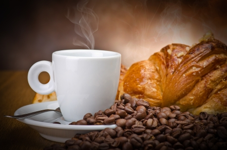 breackfast: Coffee smoking on the coffee beans and croissant background