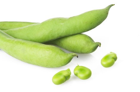 Fresh broad beans and pods close up on white