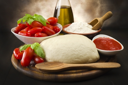 pizza ingredients: tomato, basil flour and olive oil for homemade pizza