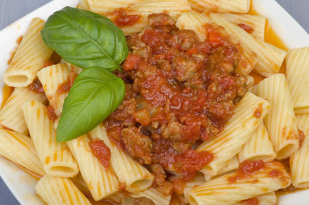 A dish of Maccheroni pasta with tomato souce and sausage photo