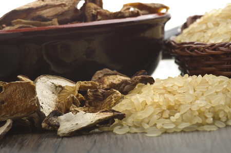 Rice and dried porcini mushrooms on table  photo