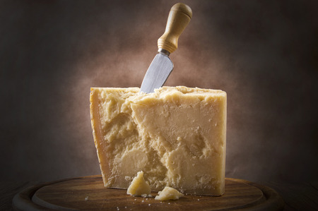 Parmesan cheese cutting on the chopping board Imagens - 25600434