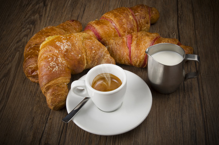 Hot coffee and fresh croissants on the wood table Imagens - 26932614