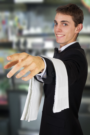 busboy: young waiter in uniform welcomes guests in store