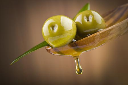 Twee olijven en bladeren met een druppel olie op houten lepel Stockfoto