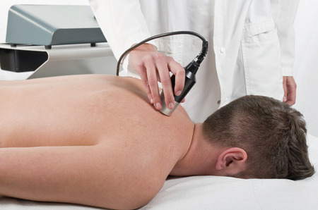 therapeutic massage: Close-up of laser treatment at physiotherapy