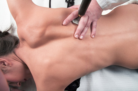 myofascial: physical therapist massages the back of the girl with tecartherapy Stock Photo