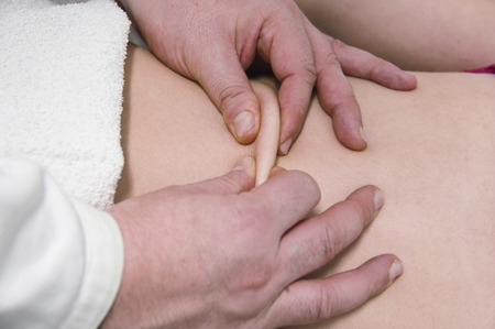 myofascial: physical therapist, massages the girl with hands
